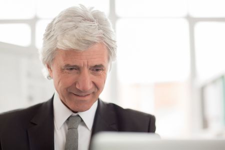 Mature wrinkled businessman with grey hair working with online information in office