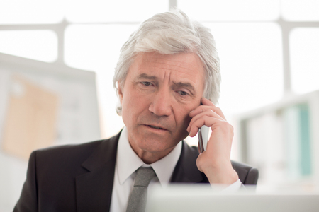 Smart mature man talking to somebody by phone while working in office