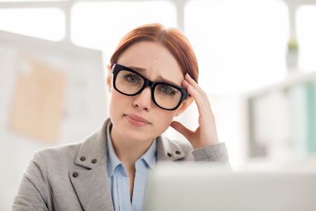 Young troubled woman looking at camera while thinking during work