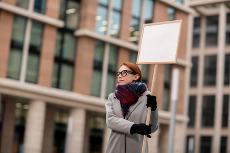 Young protestor with placard demanding raise of salary during demonstration Stock Photo