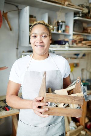 Young carpenter holding tool box with handtools and looking at camera in her workshop Фото со стока