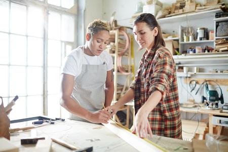 現代のワークショップで木の板を測定する2人の若い女性 写真素材 - 93743471