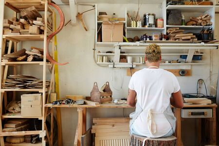 Back view of young contemporary artisan sitting by workplace on stump seat Stock Photo