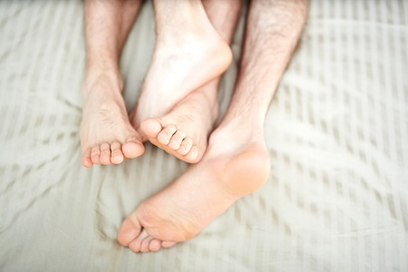 Bare feet and soles of two young gay partners sleeping together