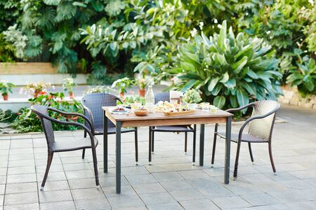 Served table with healthy organic food ready for guests in garden-room