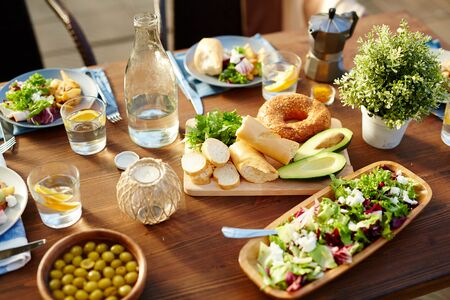 Healthy homemade food served for guests on wooden table outdoors