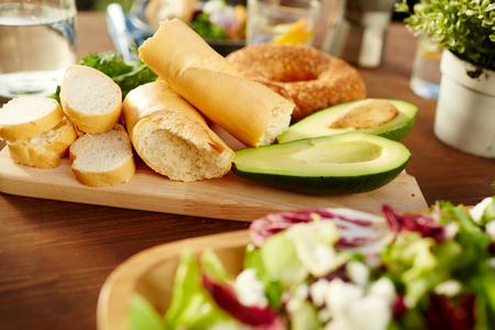 テーブルの上の木製のボード上の新鮮な小麦パンとアボカドの半分