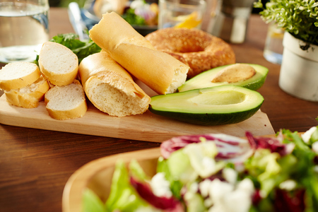 Fresh wheat bread and avocado halves on wooden board on table