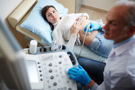 Pregnant woman looking at screen of ultrasound equipment during regular examination