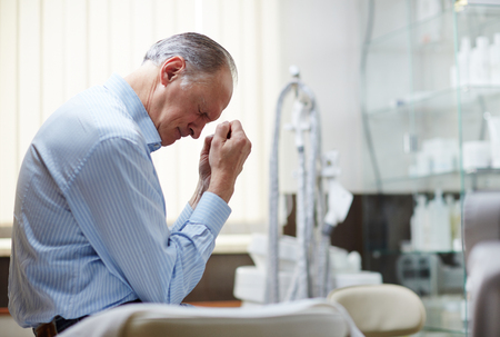 Upset senior man sitting in hospital and worrying about his diagnosis Stock Photo