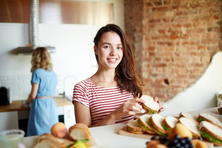 Happy woman with sandwich looking at camera while standing by served table with her friend on background