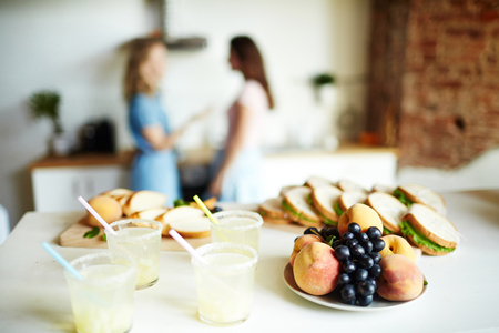 Fresh fruits on plate, homemade drinks in plastic glasses and sandwiches on table with talking girls on background