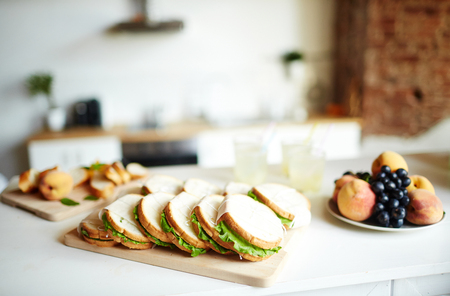 Fresh homemade sandwiches on wooden board and peaches with black grapes on plate near by Stock Photo