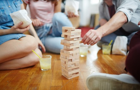 Tower of wooden bricks on the floor and several friends around it during play Stock Photo