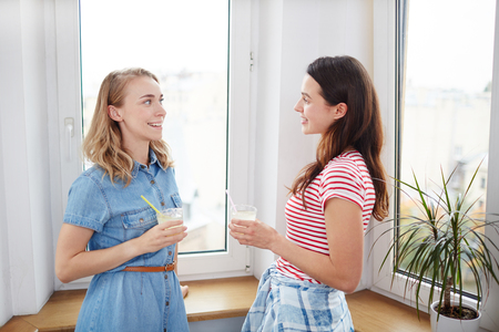 Friendly girls with drinks standing by window and talking in home environment