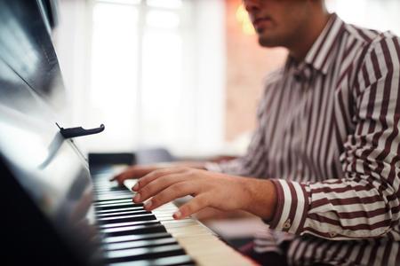 Jonge man met zijn handen over piano toetsen tijdens het spelen Stockfoto - 93877728