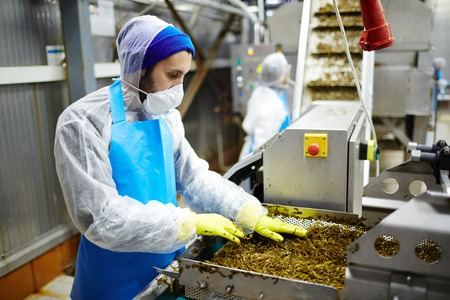 Young man in uniform working at seaweed salad producing-line
