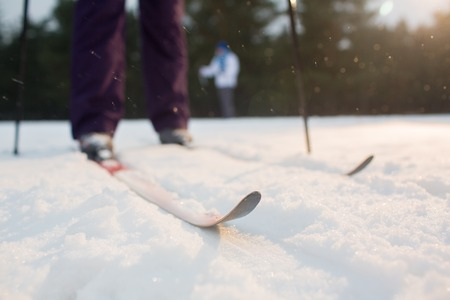 Skis on skier feet standing on snowdrift during physical activity on wintery day