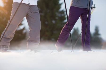 Couple of skiers in active winterwear leaning on sticks while skiing in park or forest Zdjęcie Seryjne