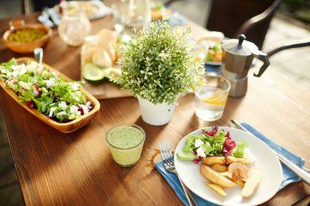 新鮮な野菜スムージー、サラダ、ローストポテトのグラス、自家製レモネード、その他の食べ物をテーブルの上に置きます。 写真素材