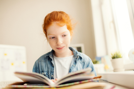 Clever little book lover sitting in library at leisure with open book in front Stock Photo