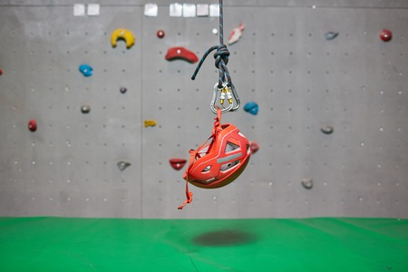 Protective helmet for climbing hanging on tight rope over green mat