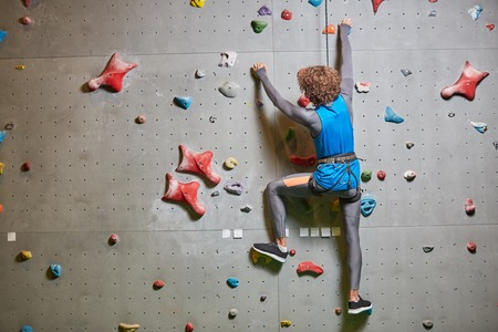 Rear view of young sportsman climbing wall while hanging on tight rope