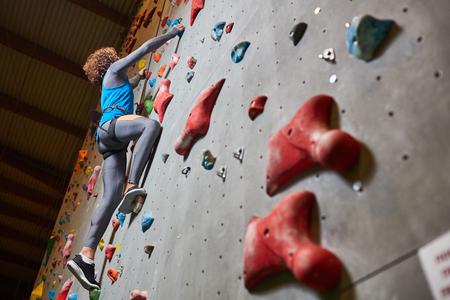 위쪽으로 이동하는 동안 벽을 등반에 그립에 의해 잡는 젊은 스포츠맨
