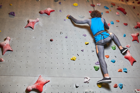 Wall for sports climbing and active guy moving upwards along it during training