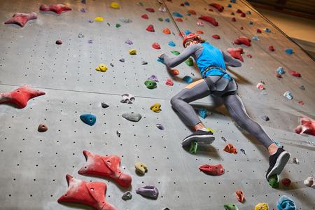 Young man in helmet and sportswear climbing upwards along wall