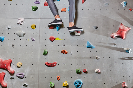 Lower part of climber legs in leggins and sports-shoes standing on grips of wall Stock Photo
