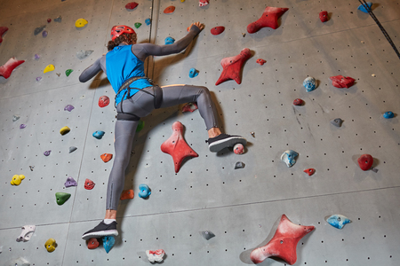 Below view of active climber in protective helmet and sportswear training on climbing wall Stock Photo