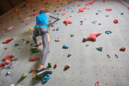 View from below of active guy during risky training on climbing wall Stock Photo