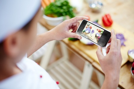Professional chef photographing fresh vegs on smartphone during work