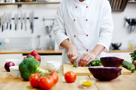 Chef of restaurant cooking fresh vegetable salad from green and red vegs Stock Photo