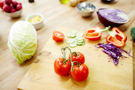 Fresh tomatoes, peppers, purple and chinese cabbage on wooden board