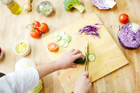 Hands of chef cutting fresh cucumber on wooden board at workplace