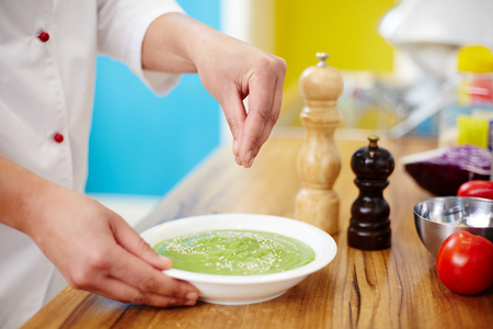 Hands of chef sprinkling fresh vegetable smoothie in plate with sesam seeds