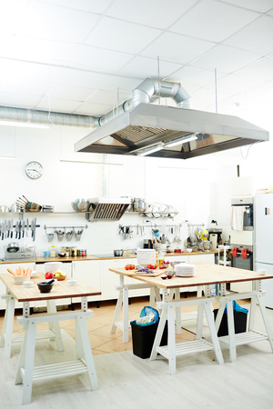 Two tables with food products and plates in empty kitchen of contemporary restaurant Stock Photo