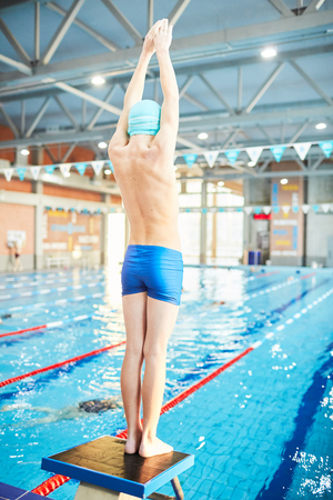 Boy in swimwear going to dive into water of swimming-pool from diving board
