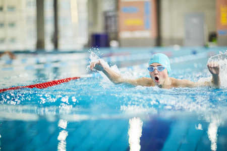 Professional swimmer splashing water while swimming energetically towards finish