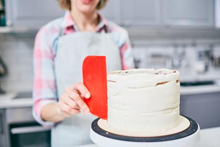 Professional foodstylist or confectioner putting marzipan glaze all over festive cake Standard-Bild