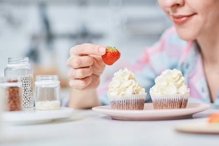 Woman putting appetizing fresh strawberry on creamy topping of cupcake
