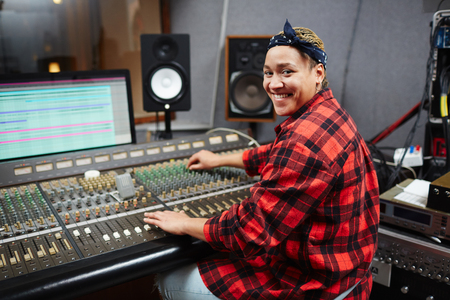 Happy young sound professional mixing sounds while working in audio studio Stock Photo