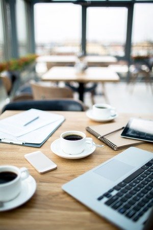 Three cups of strong black coffee, documents, notepad and gadgets on wooden table in cafe Stock Photo