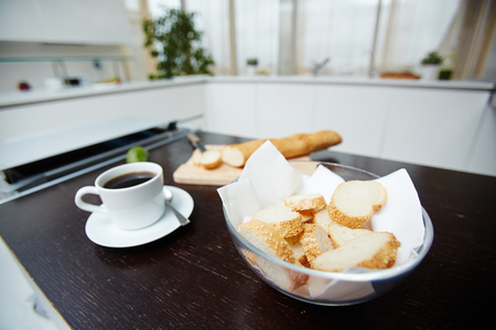 Slices of fresh wheat baguette with sesam in bowl and cup of black coffee on table in the kitchen Stock Photo