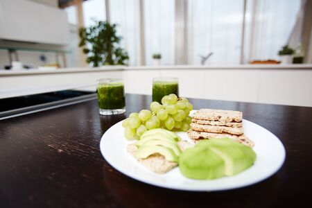 Fresh fruits and crispbread on plate and two glasses of vegetarian smoothie on wooden dinner table