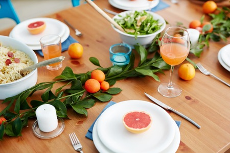 Served table with mandarins, grapefruits and cooked food prepared for guests