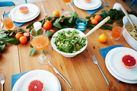 Vegetarian salad, juice in glasses, fruit decorations and grapefruit halves on plates served for guests