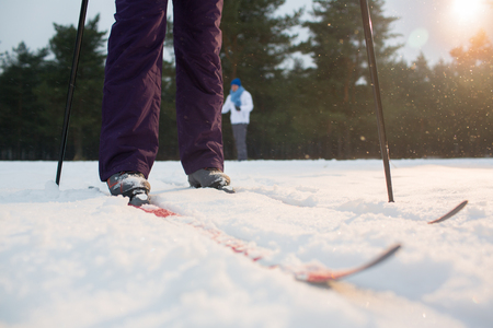 Human legs in active winterwear moving forwards along ski track while training on wintery day